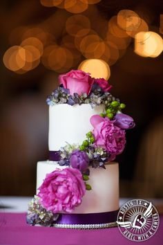 Adorable small wedding cake with purple and fuchsia floral accents at Texas Old Town.
