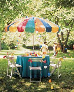Mesa de festa no jardim com guarda sol colorido e toalha azul!