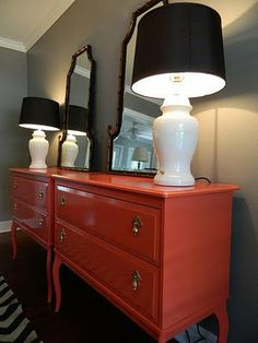 The high lacquered orange chest of drawers looks so good with the grey walls.