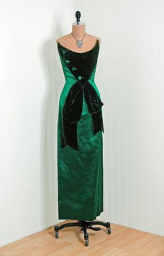 "Evening Dress, Oleg Cassini: 1950's, American, shimmer satin and silk velvet, button-trimmed bodice, draped front sash ""wiggle"" skirt."