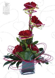 What a showstopper! Tiers of red roses surrounded by swirls of aluminum wire creates an unforgettable Valentine arrangement. Gorgeous greens and sweeping midollino sticks complete the look. #PennockFloral