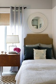Grommet curtains with burlap roller blinds/burlap headboard, and white wall with grey ceiling.