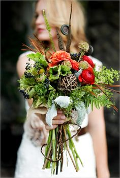 Orange roses, red ranunculus, steel berries, fern, scabious pods and feathers with twig detail