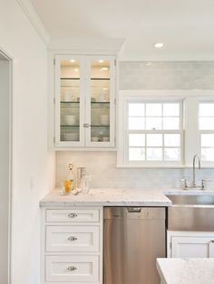 """Hampton Design - cabinetry painted """"white dove"""" - honed Carerra 2"""" eased edge countertops - Waterworks 3""""x6"""" subway tile in """"ice"""" - glass upper cabinets with interior tile - Franke stainless steel farm sink - Barber Wilson polished nickel faucets - Restoration Hardware polished nickel hardware"""