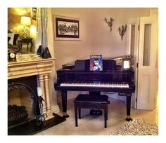 Baby grand piano tucked into corner of living room; pianist would play to the corner