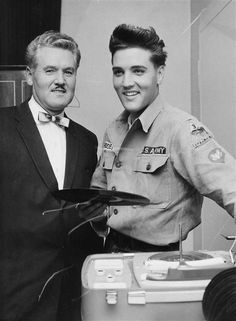 Presley at his German off-base home - Singer Elvis Presley joins his father at the record player in his off-base home here today. Presley, who drives a Jeep for the Army, hopes to be back to his entertaining job before next spring. (11/10/1959) (AP Photo)