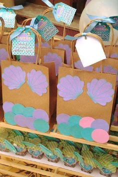 If you are the crafty type how about making your own mermaid party favor bags? All you need are some paper bags, cut-out circles, and a bunch of cut-out seashells Glue them onto the paper bag and you've got yourself a fun mermaid favor bag. You could even have your guests make their own and turn it into a party activity. See more party ideas and share yours at CatchMyParty.com #catchmyparty #partyideas #mermaidparty #mermaids #mermaidpartyideas #underthesea #mermaidfavorbags Mermaid Party Favors, Boy Party Favors, Mermaid Parties, Party Favor Bags, The Paper Bag, Paper Bags, Mermaid Under The Sea, Under The Sea Party, Boy Birthday