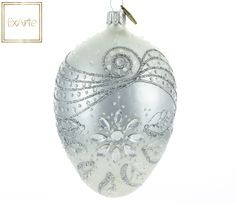 Szklane bombki choinkowe. Egg on shaded background, passing from white to silver metallic in the middle. In decoration silver elements harmonize with the original transparent convex details. In the upper part silver relief ribbon, below - a large crystal flower with petals.
