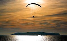 A paraglider enjoys the winter sun off the Dorset coast near Weymouth with the Isle of Portland in the background
