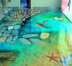 Underwater floor design by Mare Floors, Germany. To install, (1) apply a plastic layer to the existing concrete; (2) bond self-adhesive vinyl graphics to the base; (3) adhere glass beads and crystals to the printed image; (4) overlay with a matte covering and, finally; (5) to create a look of shimmering water, install a hard-wearing transparent film.