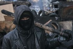 An anti-government protester, charred weapon resting on shoulder, stands on a barricade in Kiev. http://www.vocativ.com/02-2014/faces-kiev/