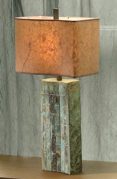This handsome, substantial lamp has a slightly curved base crafted from a mosaic of natural slate tiles. The undulating shade is cinnamon-colored paper; at the top is a slate finial.