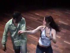 """Neste vídeo de 2008, o famoso professor Moskito pratica um samba rock clássico com """"nós de salão"""".  Durante boa parte da dança a dama é conduzida com apenas um braço. As movimentações em que ela é conduzida com os 2 braços conectados produzem enlaces de complexidade intermediária que são feitos e desfeitos sempre no ritmo da música (nós de salão)."""