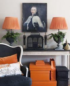 charming arrangement with black cage, portrait, chair and orange accents