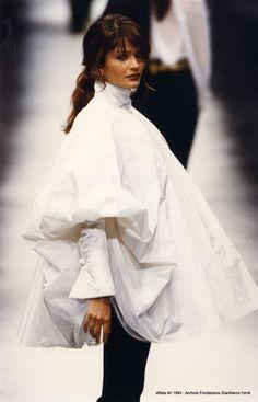 D'Artista 1993 Il progetto della camicia riunisce alcuni elementi della moda del tardo Ottocento: l'aderenza al corpo del colletto e dei polsini, le ricercate rifiniture (trina, ricamo meccanico) ed infine l'enfasi dei volumi delle maniche. La confezione è basata sul taglio a ruota di tre teli. I tessuti esterno e intermedio sono di taffetas, quello interno è di organza. una delle 27 camicie di G.Ferrè