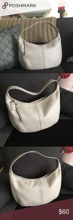 COACH white leather hobo Used. Lightweight and roomy. Interior is lined in light blue fabric has large zipper pocket and 2 slip pockets. Some ink spots at the bottom. Exterior clean lines, and simple no pockets. Some normal wear in the leather. Mostly on the handle and by the zipper. The pull tab also has some wear but over all in good condition. No rips or holes. This would be more M/L size Coach Bags Hobos