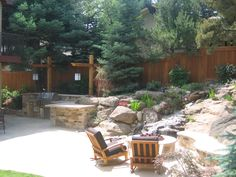 This stone patio is bordered by natural boulders and a water feature on one side, and built-in outdoor kitchen on the other. Plantings screen the patio from neighbors, creating a sense of privacy and intimacy. By Native Edge Landscapes in Boulder, Colorado.