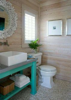 Love the aqua table, wood panneling and pepple tiles. Such a lovely beachy vibe!