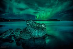 Cosmos - Every year, the skies in Iceland celebrate the Northern Lights. At the growler beach near Jökulsárlón in southern Iceland, we photographed the spectacle of the Aurora Borealis (Northern Lights) dancing over and reflecting off of growlers (icebergs) calved from the glacier that had run aground.  #Aurora #Borealis #green #skies #nature #photography