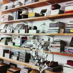Long, wooden shelves hold books, frames, and other memorabilia in an unconventional way. Love it!