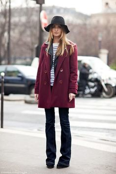 Woman on street wearing flared jeans with an oxblood coat and a black floppy hat