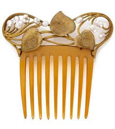 AN ART NOUVEAU PEARL AND 18K YELLOW GOLD COMB, CIRCA 1900. A horn comb surmounted by an 18k yellow gold foliate design, adorned with leaves and freshwater baroque pearls.
