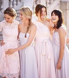 Four women in pink and lilac-grey bridesmaid dresses on stone staircase