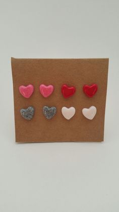 Dainty heart-shaped studs in pink, grey, red, and white. These simple stud earrings are 100% hand made in my home studio. They are crafted from baked, non-toxic polymer clay and glazed with a gloss gl