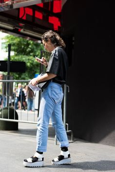 Womenswear Street Style by Ángel Robles. Fashion Photography from Milan Fashion Week. Woman on the street wearing mom jeans, leather shirt and white platform sandals before MSGM show, Milano.
