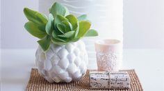 Attach sea shells of the same shape and color onto a plain glass container for a beach-inspired vase. Get the tutorial at Home Life.   - CountryLiving.com