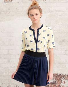Falda plisada azul marino y blusa de palmeritas.