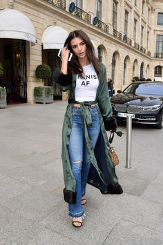 "Emily Ratajkowski is ""Feminist AF."" How do we know that? Today in Paris, she stepped out in an army green silk robe by up-and-coming label Cinque, low-slung denim jeans, heeled sandals, a Tory Burch bag, and a Jonathan Simkhai white T-shirt that had the all-caps message ""Feminist AF"" stamped on the front."