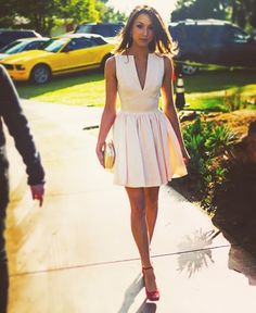 Acheter la tenue sur Lookastic: https://lookastic.fr/mode-femme/tenues/robe-patineuse-escarpins-en-daim-rouges-pochette/2904 — Pochette dorée — Escarpins en daim rouges — Robe patineuse rose