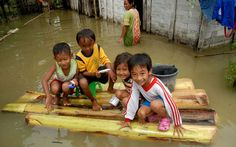 Children play on a raft made from banana trees in front of flooded houses in the village of Truni in Indonesia