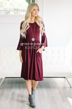 This dress is so soft and comfy you will want to wear one everyday. Solid burgundy dress features a round neckline, 3/4 length bell sleeves, an elastic waist and side seam pockets.