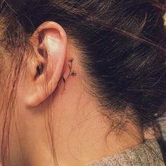 tattoo hinterm ohr - eine junge frau mit einer kleinen schwarzen tätowierung mit kleinen schwarzen blumen