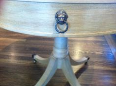 Round side table with lions head pulls