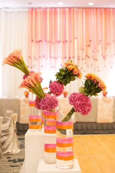 Create height and dimension with these lopsided floral bouquets as decor for a reception.  Flowers used: Pink hydrangeas, orange lilies, and orange roses.   Photo Gucio Photography