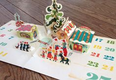 Ray Marshall - http://raymarshall.com/2013/09/yuletide-carolers-pop-up-advent-calendar-now-available/