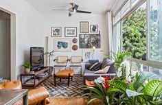 A sala de estar desse apê compacto conta com muitas plantas e peças de design.