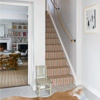 White traditional hallway with striped stair runner