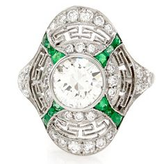 Art Deco round brilliant cut diamond and modified french cut emerald shield ring set in platinum. The center diamond (0.94ct) is K in color and SI3 in