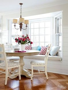 Despite having to move a register to make it happen, a new window seat provides comfy mealtime seating and storage. The dining table and chairs were found on Craiglist and updated with a distressed paint treatment and patterned seat covers. The homeowner installed the charming chevron cork floor tiles herself./