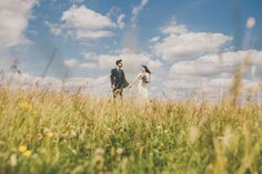 Bride & Groom, on their wedding day, stood in a field full of summer & spring flowers, in the sunshine, under clouds. Helmsley in Yorkshire.
