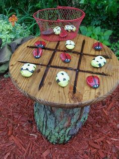 tic tac toe tree trunk table with stones painted as bees and lady bugs. I like the bugs!