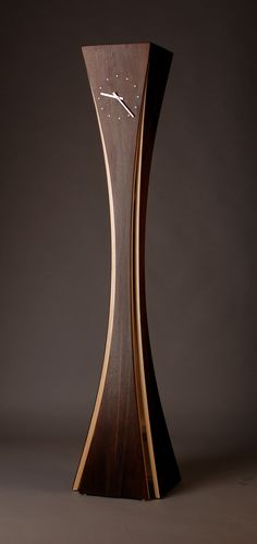 """Vega Clock"" created by Kyle Dallman Black walnut and aspen wood are used in a bent lamination technique. The legs are then mitered together at the top."