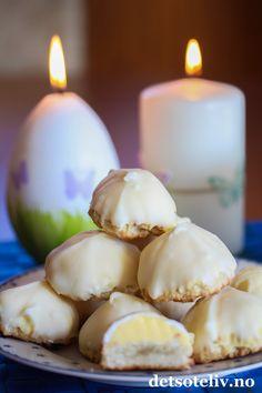 """""""Biskvier"""" er svenske kaker som består av små makronbunner som dekkes med krem og som deretter dyppes i smeltet sjokolade. Konseptet er det samme som de velkjente kakene""""Sarah Bernhard"""" er basert på. I Sverige varierer man imidlertid Biskvier med ulike typer fyll og sjokoladetrekk. Her har du en variant som består av myke marsipanmakroner som dekkes med sitronkrem og deretter dyppes i smeltet, hvit sjokolade. Svenske """"Citronbiskvier"""" er virkelig nydelige konfektkaker!"""