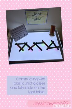 Constructing with plastic, coloured shot glasses and lolly sticks. EYFS