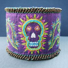 Day of the Dead Embroidered Cuff    Inspired by the wonderful embroidery of Mexico and the Day of the Dead, I designed and embroidered this colorful cuff. Starting with iridescent purple dupioni silk with teal overtones, I embroidered a bright skull surrounded by a floral motif using cotton embroidery floss. The silk was backed by fabric interfacing to give it a little bit of stiffness. After the embroidery was done, the entire cuff was lined with dark purple ultrasuede, which is very soft…