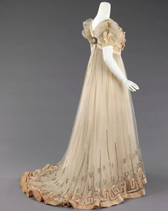 Evening Dress House of Paquin 1905-07 Produced several years prior to the 1908 Hellenic designs of Paul Poiret, the raised waist and decorative references to Greek antiquity indicate this classical aesthetic and change of silhouette were in the air from 1905 on. As the leading house of couture druing the Belle Epoque, Paquin's promotion of this line would have been widely known to the public. The dress also incorporates signature decorative techniques such as velvet piping outlining peach…
